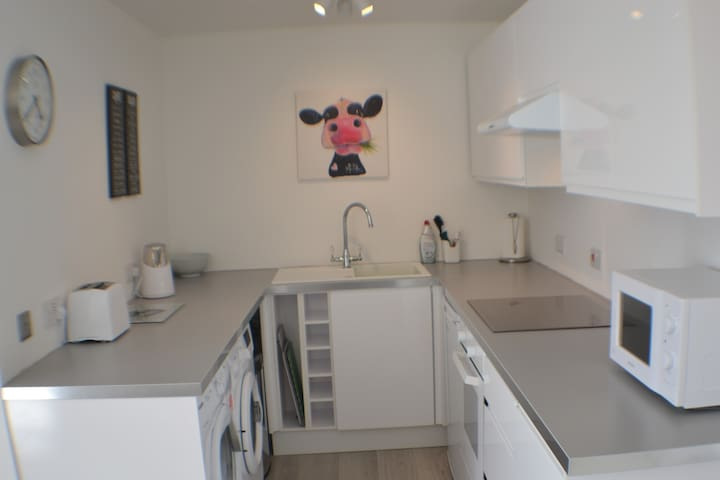 Fully equipped kitchen with full sized oven and hob, microwave, washing machine, dryer, fridge with ice box, kettle, toaster.