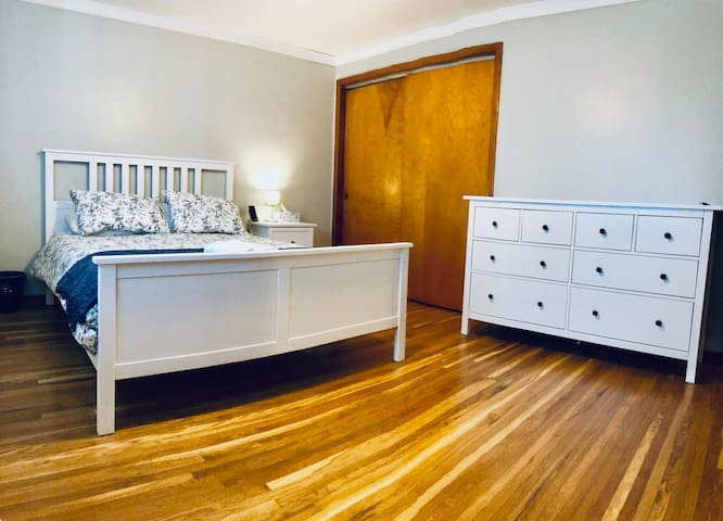Master Bedroom with a comfortable queen size bed, fresh linens, hardwood floors, light blocking curtains, rocking chair, and full sized mirror.