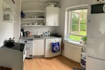 Køkken med opvaskemaskine, køleskab, komfur og mikrobølgeovn