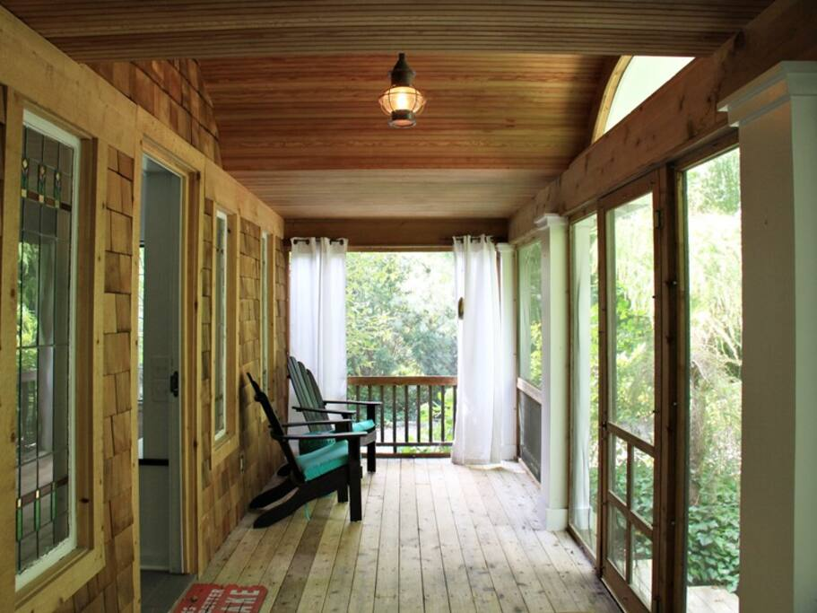 Huge screen porch with chairs at one end...