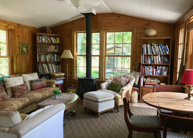 Living room with a gas wood stove, comfortable seating, books, games, and a bistro table.
