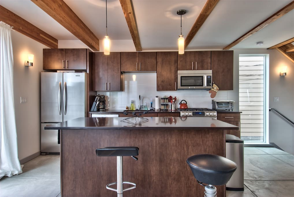 full stainless kitchen with island, gas range, and dishwasher