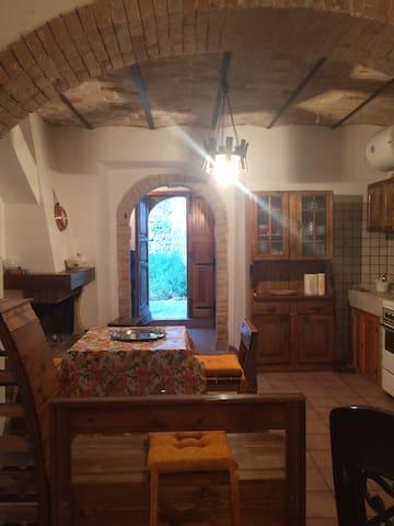 Il salone con il camino e la zona cucina