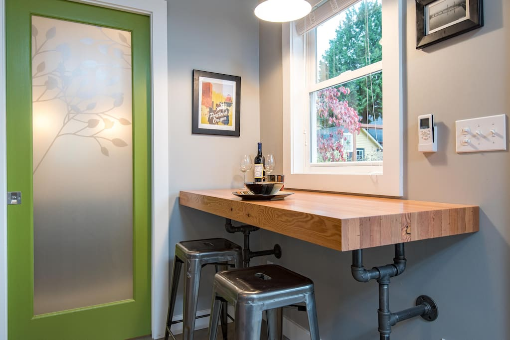 Salvaged wood slab bar with vintage pipe brackets, great spot to sip morning coffee, work on your laptop or just hang out. Frosted glass pocket door leads back to secluded bathroom.