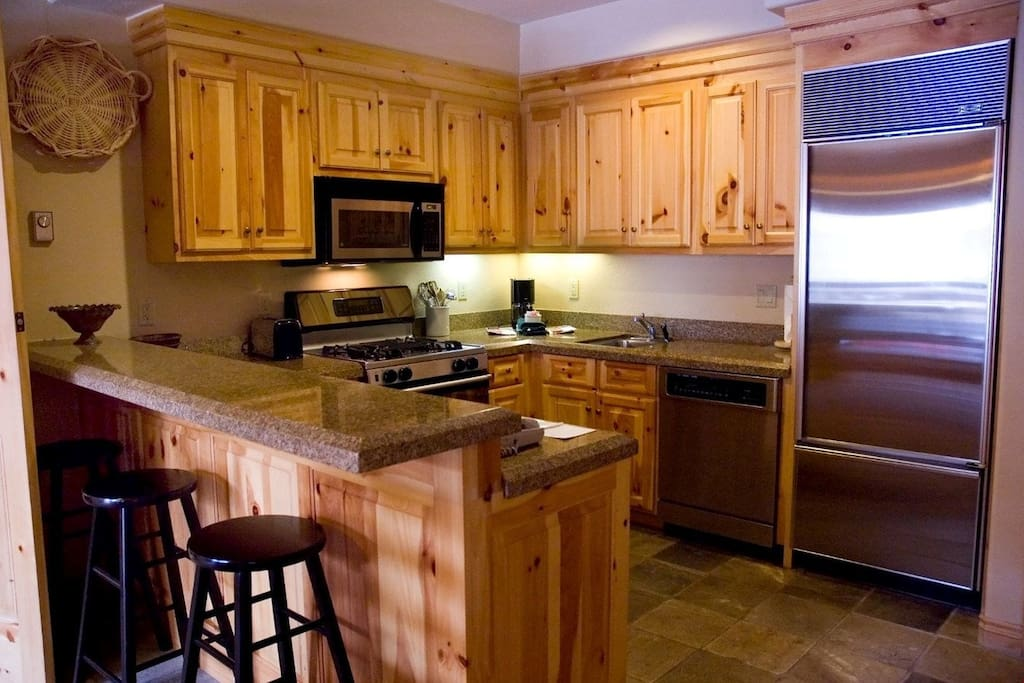 The fully-equipped kitchen has modern appliances and beautiful wood touches