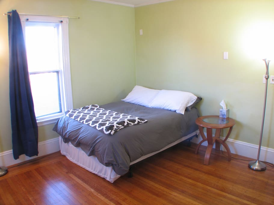 Full size bed, bedside table, and sunlit window