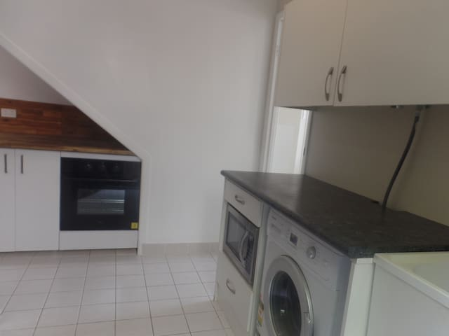 Granny Flat Kitchen / Laundry showing Wall Oven with grill, Microwave, Washing Machine and Sink. Portable Hot Plate, Portable, Frying Pan with pots, Kettle and Toaster also included as well as crockery, cutlery, etc.
