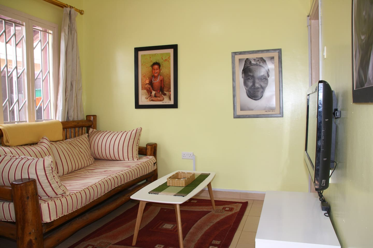colorful living room with African photography, large 42 inch screen TV, cable , DVD player.