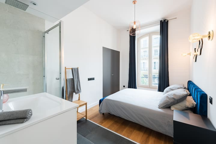 """Chambre type """"suite"""" avec lit double, placard de rangement et espace salle de bain"""