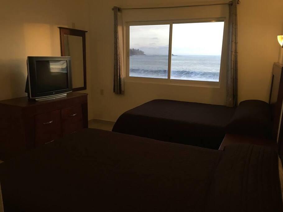 Habitación con dos camas matrimoniales, vista a la playa