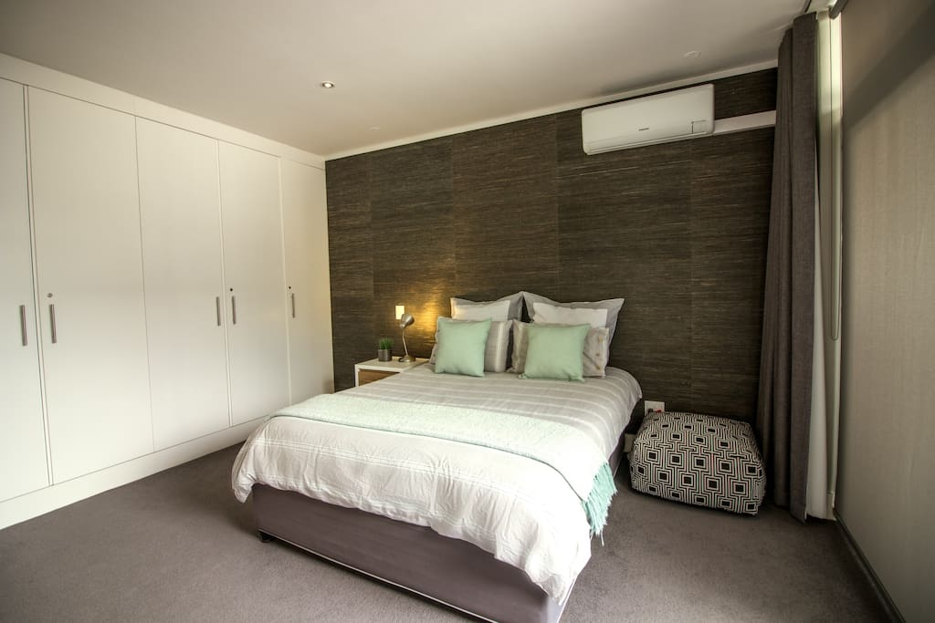 Modern, spacious bedroom with queen bed, air conditioner and cupboards