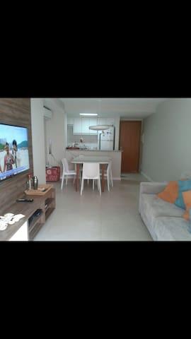 Imagem da sala, com sofá retrátil, televisão smart e mesa de jantar.