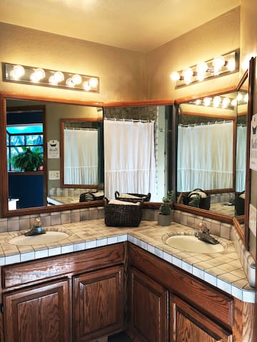 Full bathroom with fan and double sink.