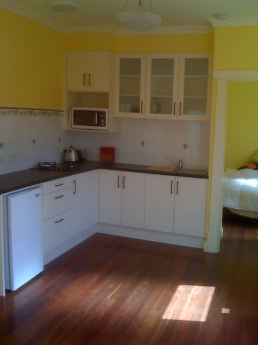 Kitchen area with ample storage, and bench top, cooktop, fridge, microwave,sink , toaster, kettle and expresso coffee pod machine