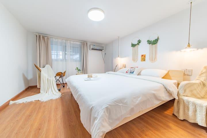 卧室1—带独立的门,1.8米的大床、软硬舒适的床垫、蝴蝶椅、单人沙发、遮光窗帘