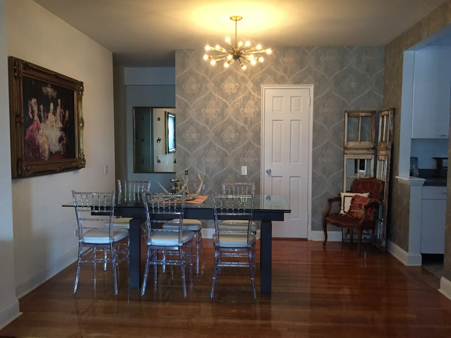 Wallpapered dining room with custom chandelier ,original oil painting and antique mirror. Beautiful table-seating for 8 (table extends and extra seats are in closet)