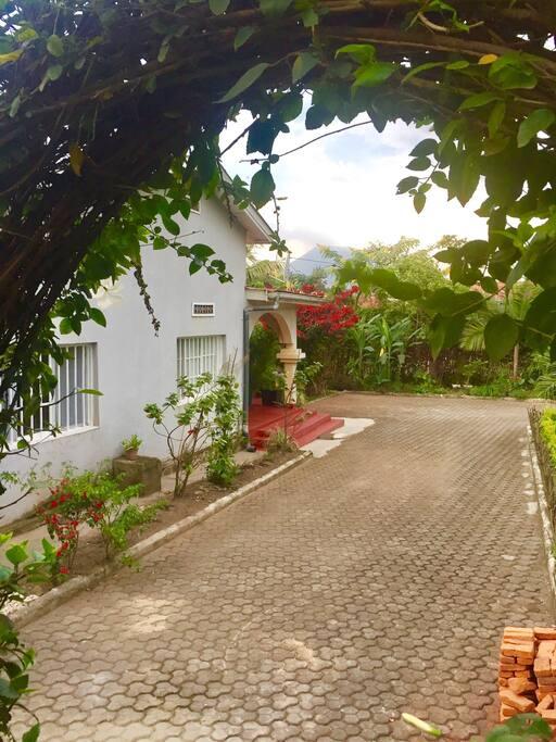 La maison vue du jardin et le volcan au fond.