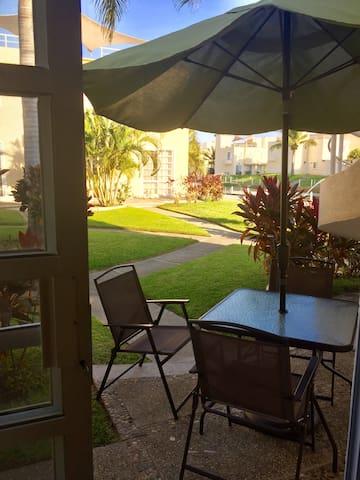 Terraza en espacio privativo, cuenta con sombrilla, mesa y 4 sillas