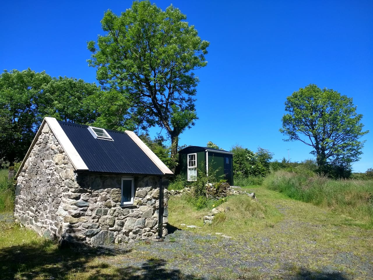 Shepherd's hut and stone building with shower and kitchen.