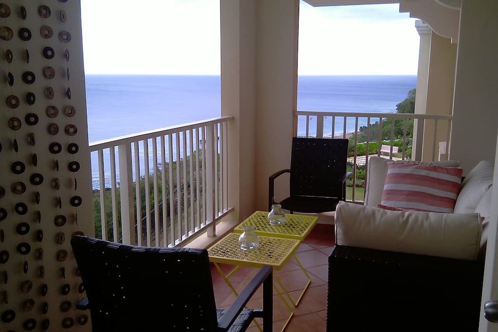 Balcony with seating area for relaxing and enjoying ocean view.