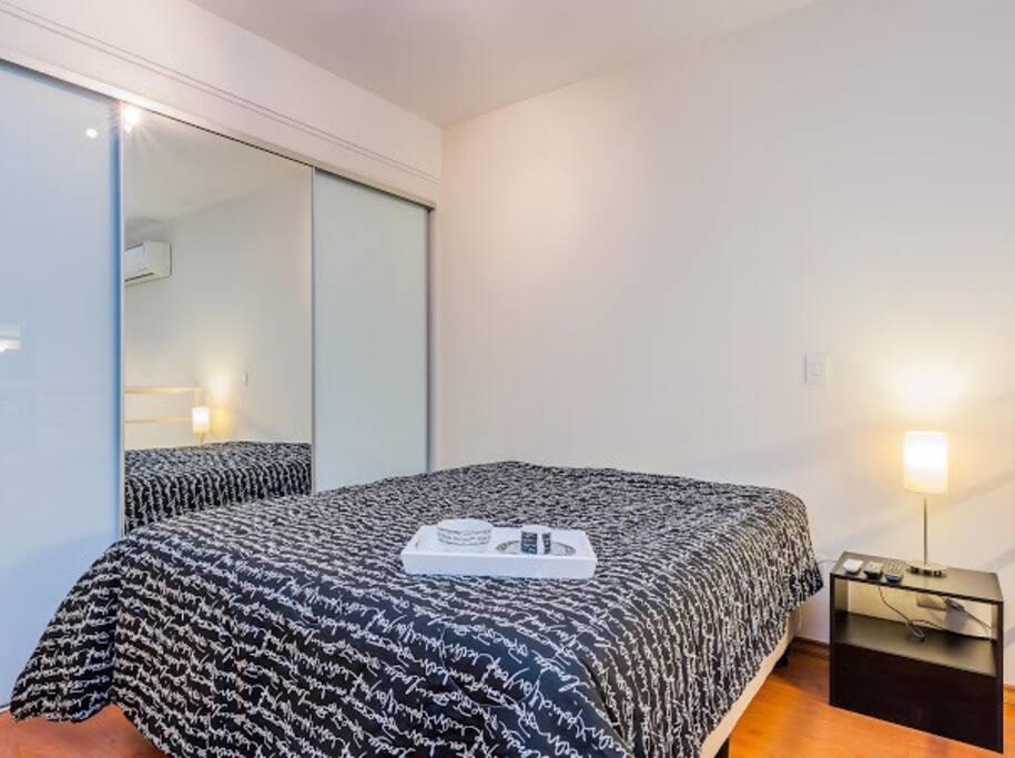 Quarto com cama queen size padrão hotelaria. Armários planejados 3 portas com espelho.