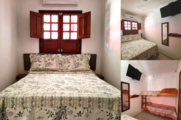 Quarto com ar-condicionado, tv a cabo, cama de casal e beliche.