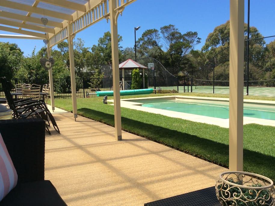 View from Bungalow verandah across lawn to heated pool and tennis court.
