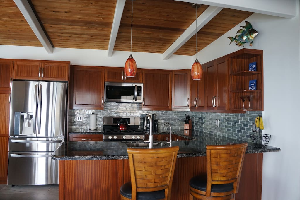 Custom gourmet kitchen with tropical mahogany cabinets
