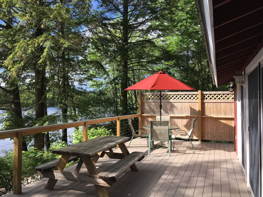 The deck runs along the entire lakeside of the cottage.  Grill is at the end opposite the umbrella table.