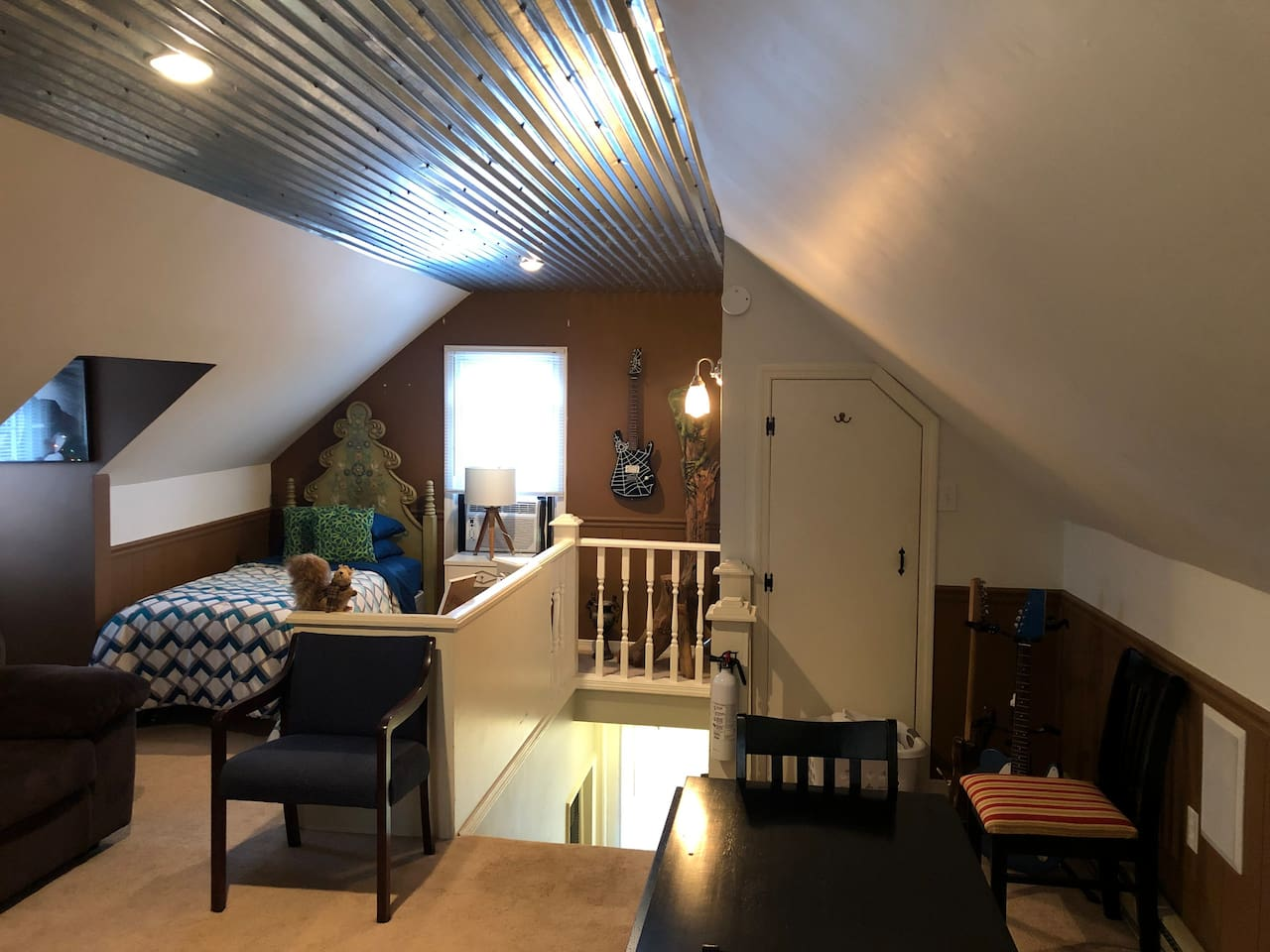 The barn tin ceiling and recessed lighting makes this groovy space full of musical instruments even more cool!