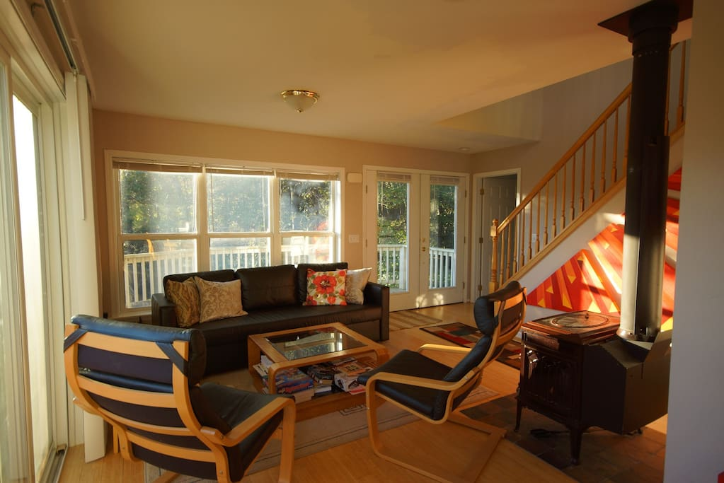 Open main floor living room with lots of windows, wonderful views and woodstove.