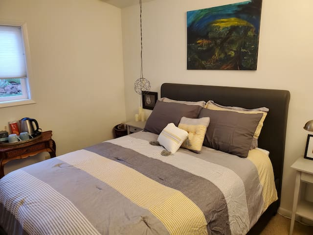 Light-filled guest room with queen bed.