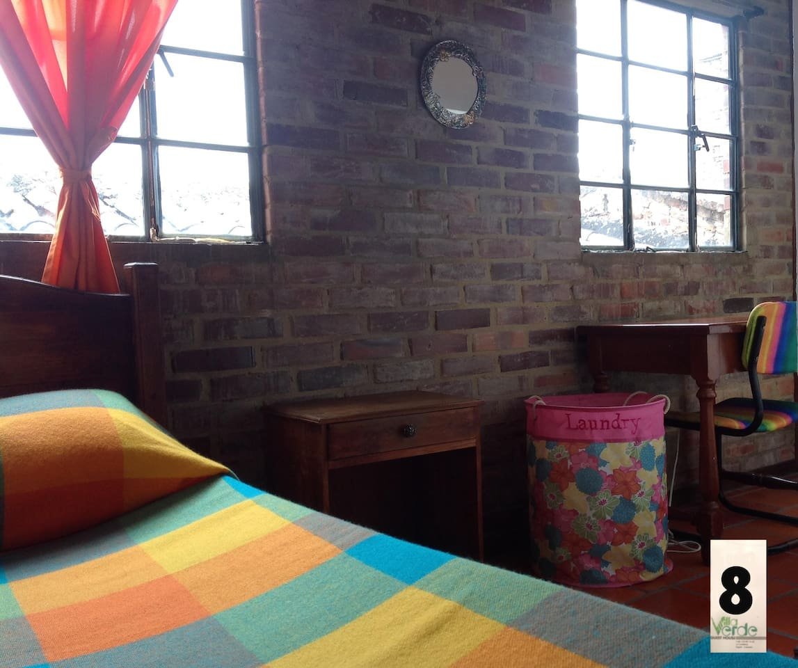 Each of our bedrooms contains big drawers, twin bed an a small desk with enough lightning for private study. We are a guest house located in the heart of the downtown district in Bogotá (Colombia), in a 100 year old house, recently renovated and still own for a long lineage of family members. We are proud of being bogotanians and we make a real effort to make you feel comfortable and welcome. It´s literally 5 minutes walk from everywhere. (MUSEO DEL ORO, ESTACION AGUAS, CASA DE POESIA SILVA, BIBLIOTECA LUIS ANGEL ARANGO, UNIVERSIDAD DE LOS ANDES, UNIVERSIDAD DEL ROSARIO). The common areas are the kitchen, and 2 more cosy places to interact with the rest of the tenants (2 balconies, one with a breathtaking view to the mountains with a BBQ at the top of the third storey, another more intimate at the second floor and a living room with Direct-tv) also we provided high-speed WI-FI. We handpicked our tenants in order to ensure a safe and sound environment. Most of our tenants are young students/professionals from all over the world). We prefer long term rentals. Thank you for watching.