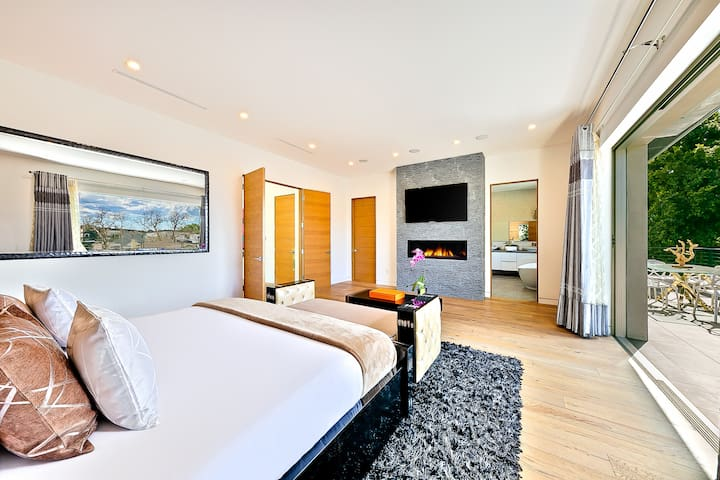 """Master Bedroom with King size bed,  High end Italian furniture with fireplace, 75"""" TV, opening to a huge balcony with dining table."""