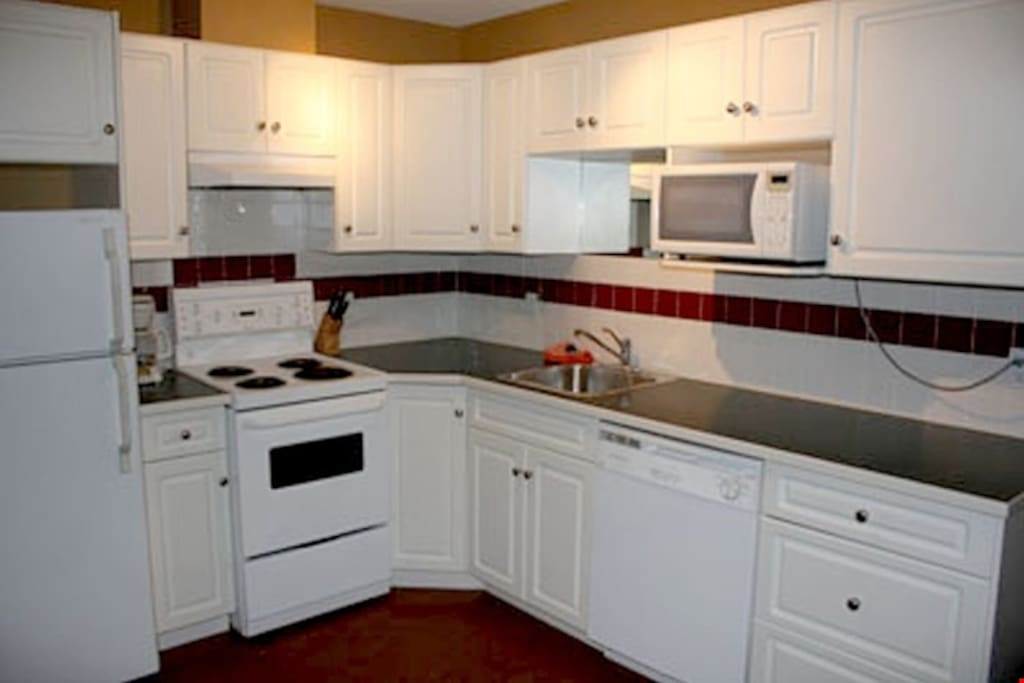 The kitchen features a stove, oven, microwave, dishwasher, fridge and coffee maker.