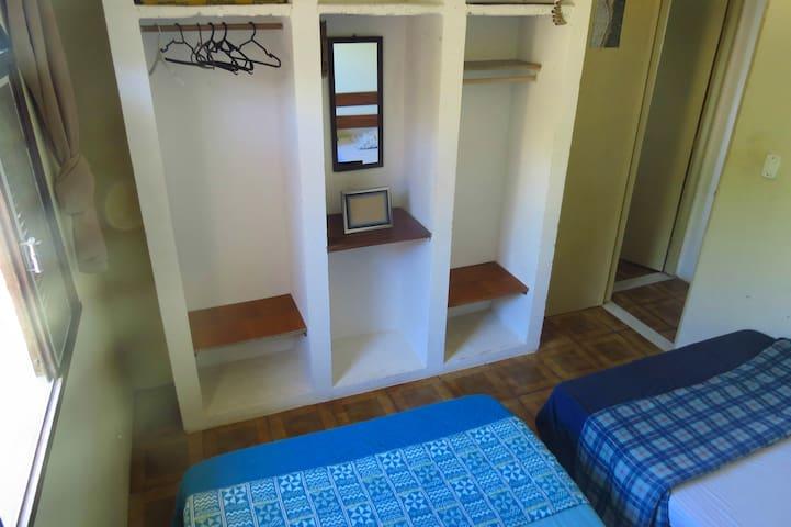 Quarto com duas camas de casal, guarda-roupa, ventilador de teto e vista lateral para o mar!
