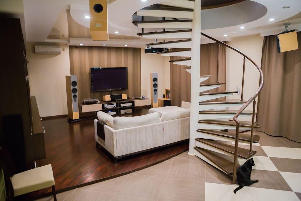 """Просторная гостиная с большим диваном с 60"""" телевизором с стерео системой."""