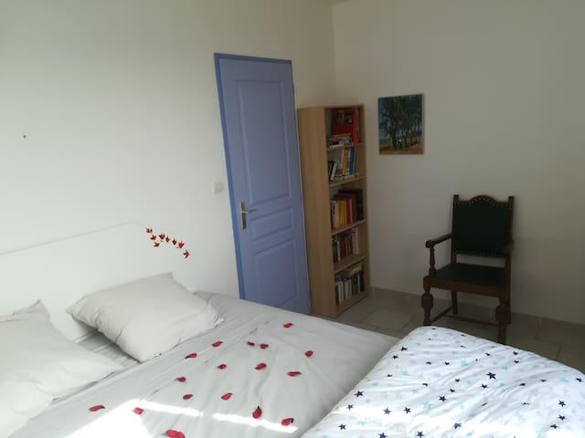 Chambre lune de miel avec lit en 160. Joliment décorée avec des pétales de roses étalées sur le lit. Vue globale (1/3)