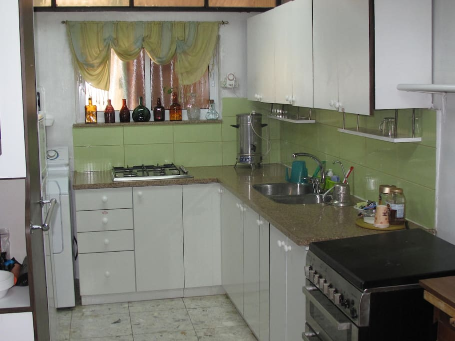 Kitchen with double stainless steel sinks and stove top.