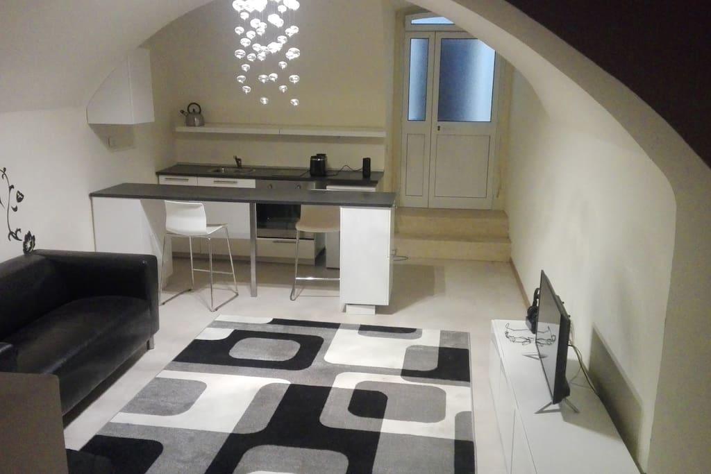 soggiorno superiore con tappeto  infinito otto  e cucina ad induzione total white