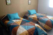 Recámara con 2 camas individuales, librero, amplio closet y acceso directo a baño completo.