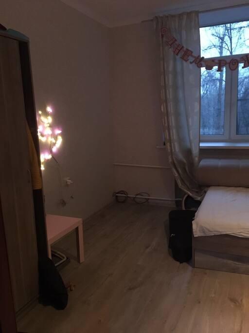 Спальня с двухспальный кроватью, шкафом, столом и окном в Нескучный сад