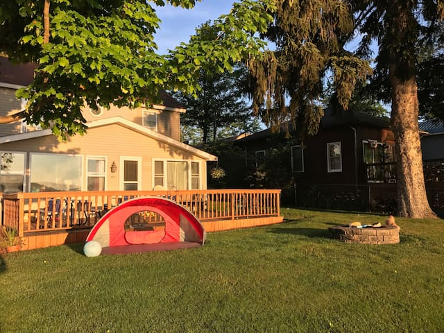 Front of the cottage with lots of sunshine! The cottage faces east so you get early morning sun and it stays for the entire day. Fire pit available as well as a tent to keep littles ones out of the sun.