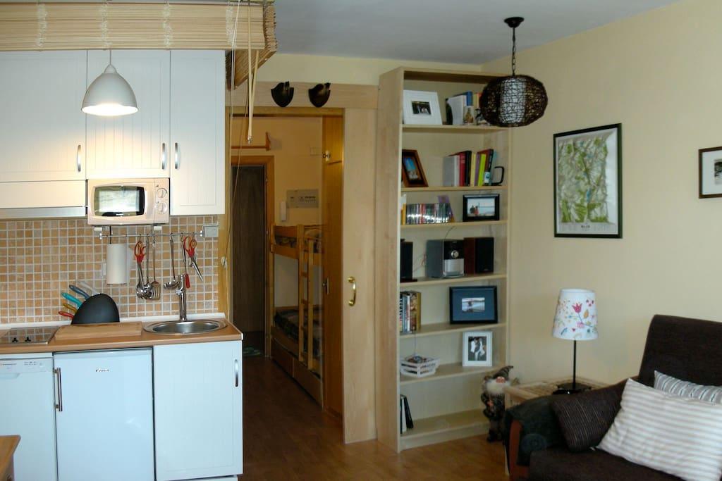 Salón con cocina incorporada y puerta corredera