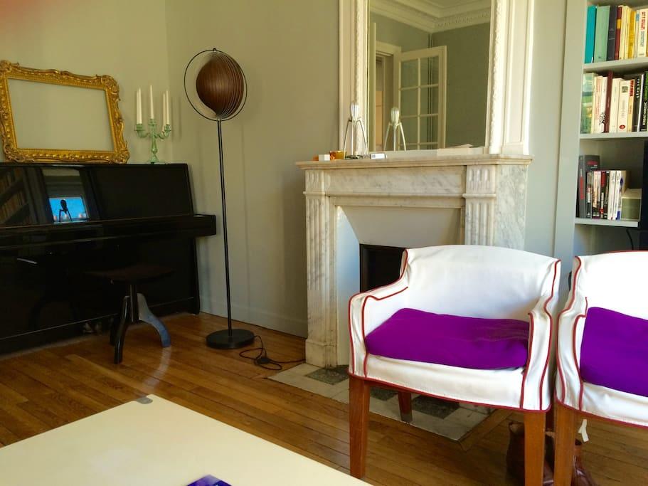 Salon avec piano et cheminée