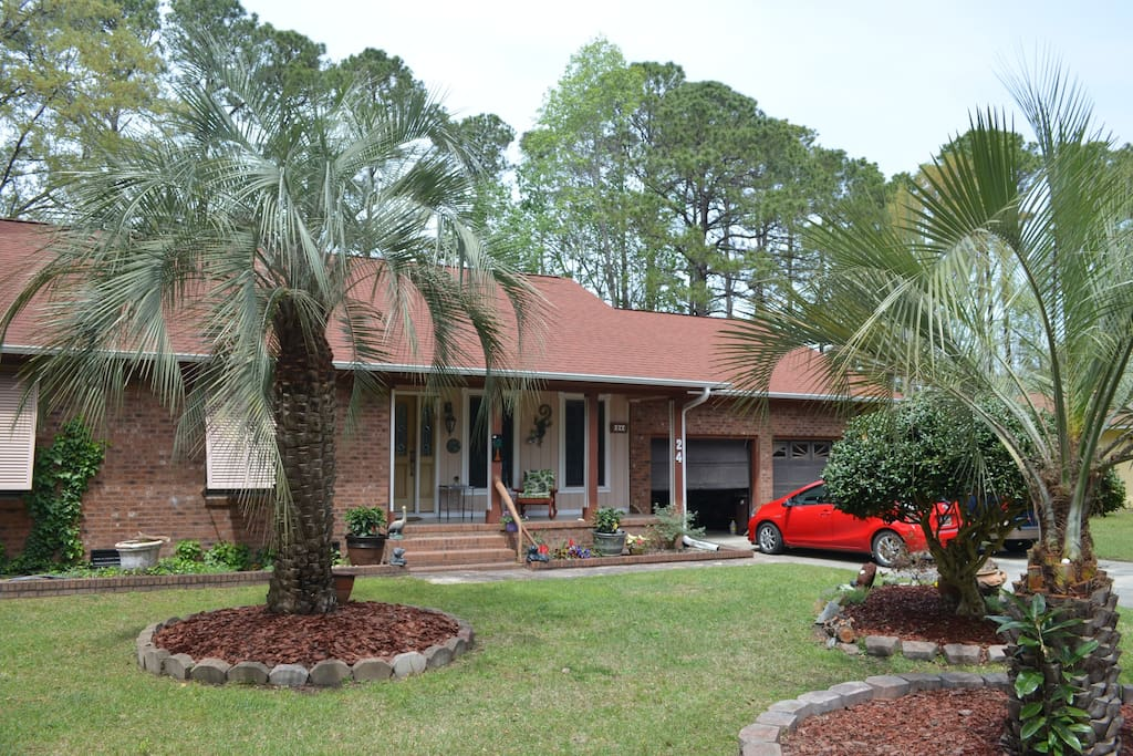 Front of the home with ample parking, covered front porch and native landscaping.