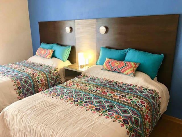 Habitación principal con dos camas matrimoniales y baño completo compartido con el estudio. Toma 1