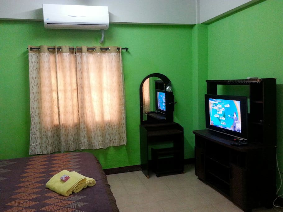 A spacious studio with a big bed,  air con, flat screen TV,  fridge, microwave,  table & chairs