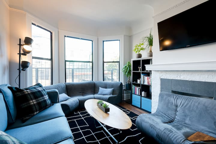 Light-filled shared living room with bay window and couches designed + crafted by the host.