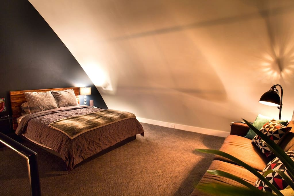 The upstairs loft bedroom is furnished with a comfy queen platform bed and pillow-top mattress.